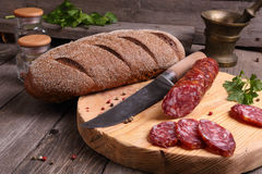 Salami, bread and a knife on the  table Royalty Free Stock Image