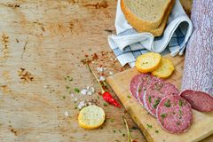 Salami and bread. Bread slices and Bruschetta with Salami and spices as a rustic lunch royalty free stock photo