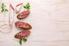 Salami and bread on white wooden background. Top view. Copy space stock photo