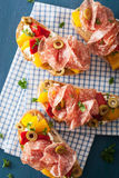 Salami bruschetta with roasted peppers goat cheese olives Stock Photo