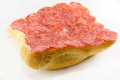 Salami on a bun. On a white background Stock Photography