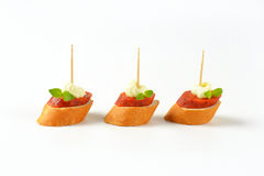 Salami canapes. Three canapes with pepperoni salami and whipped cream on white background royalty free stock image