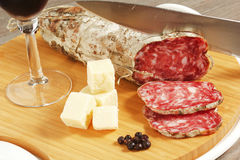 Salami and cheese. On a wood table Royalty Free Stock Photo