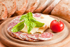 Salami, cheese, bread ciabatta, basil and tomato. Focus on foreground Royalty Free Stock Photography