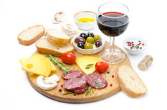 Salami, cheese, bread, olives, tomatoes and glass of red wine Stock Photos