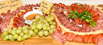 Salami and cheese composition. Italian salami and cheese with honey and grapes Royalty Free Stock Images