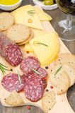 Salami, cheese, crackers, olives and a glass of wine on board Royalty Free Stock Images