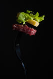 Salami, cheese and lettuce on a fork Royalty Free Stock Photo