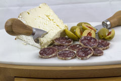 Salami, Cheese and Olives. Serving of salami, cheese and olives as an horderve before dinner Royalty Free Stock Photo