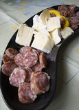 Salami and cheese plate. A plate of salami slices with some cheese bits stock photo