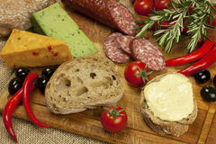 Salami and cheese platter with vegetable and herbs Royalty Free Stock Photos