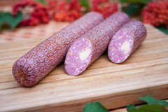Salami with cheese on a wooden board. Salami with cheese filling on a wooden board close up royalty free stock photo