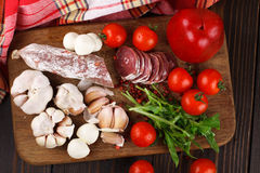 Salami with cherry tomatoes, pepper, garlic and ruccola on a cut Royalty Free Stock Photography