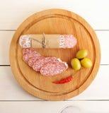 Salami, chili i oliwki na drewnianym tle, zdjęcia stock