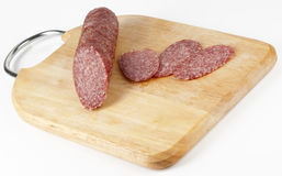 Salami on chopping plank Royalty Free Stock Photo