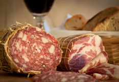 Salami close-up. Close-up on delicious salami. Bread and wine in the background Stock Photos