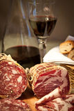 Salami close-up, portrait. Close-up on delicious salami. Bread and wine in the background. Portrait orientation Stock Photography