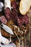 Salami cortado del ‹del †del ‹del †en tabla de cortar de madera con el cuchillo foto de archivo libre de regalías
