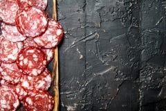 Salami cortado na placa de madeira imagem de stock
