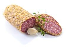 Salami coupé en tranches avec l'ail et le thym d'isolement sur le fond blanc Images stock