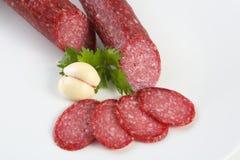 Salami coupé en tranches d'isolement avec l'herbe Photographie stock libre de droits