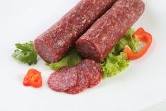 Salami coupé en tranches d'isolement avec le piment et l'herbe Photos libres de droits