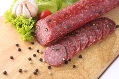 Salami coupé en tranches d'isolement avec le piment et la tomate Photos stock