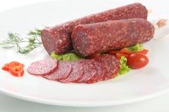 Salami coupé en tranches d'isolement avec le piment et la tomate Image stock