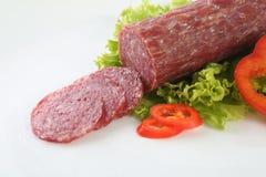 Salami coupé en tranches d'isolement avec le piment et le poivre Photographie stock