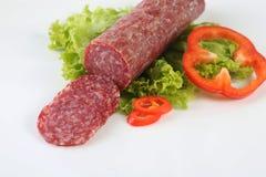 Salami coupé en tranches d'isolement avec le piment et le poivre Photographie stock libre de droits