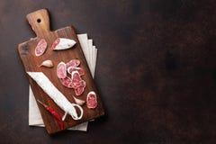 Salami coupé en tranches sur la planche à découper images stock