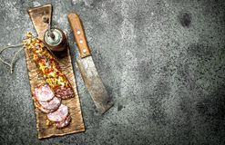 Salami on a cutting board with an old hatchet. On a rustic background Stock Image