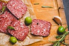 Salami délicieux avec des olives, des épices et le romarin Photographie stock libre de droits