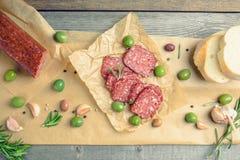 Salami délicieux avec des olives, des épices et le romarin Image libre de droits
