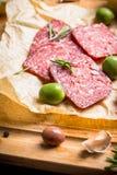 Salami délicieux avec des olives, des épices et le romarin Photo stock