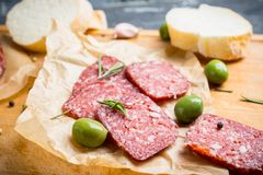 Salami délicieux avec des olives, des épices et le romarin Photographie stock