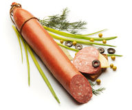Salami decorated with onion, dill, olive and pie. Over white background Royalty Free Stock Images