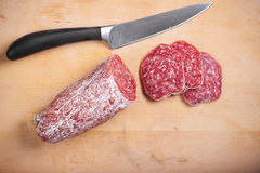Salami on the desk. Slices of salami on a real desk with a knife royalty free stock photo
