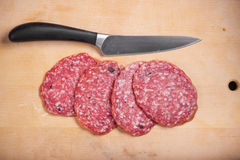 Salami on the desk. Slices of salami on a real desk with a knife stock images