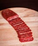 Salami die op hakbord wordt gesneden stock afbeelding