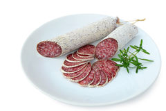 Salami -  dried sausages on plate. Winter salami -  dried sausages on a plate isolated on white background Stock Images