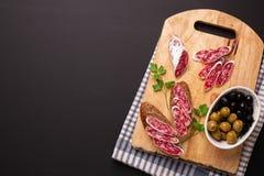 Salami en brood op zwarte achtergrond Hoogste mening Royalty-vrije Stock Foto's