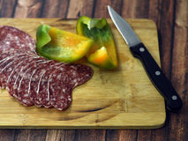 Salami et paprika de plat en bois Images stock