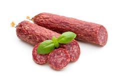 Salami gerookte worst, geïsoleerde basilicumbladeren en peperbollen stock foto