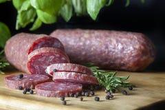 Salami geschnitten auf hölzernem Brett Lizenzfreies Stockfoto