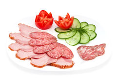 Salami and ham. Sliced salami and ham with cucumber and tomatos on a plate isolated on a white background Royalty Free Stock Photography
