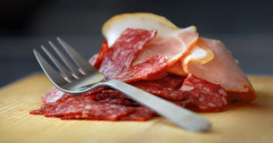 Salami and ham. On board is the kitchen fork, salt and ham Royalty Free Stock Image