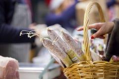 Salami im Korb auf dem Markt Stockbilder