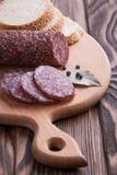 Salami italiano cortado en la tabla de madera Imagenes de archivo