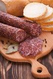 Salami italien coupé en tranches sur la table en bois Image libre de droits